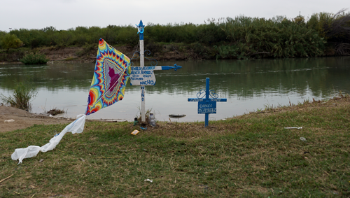 A cross with a kite attached to it marks where a child died tried to make it into the United States by crossing the Rio Grande in Nuevo Laredo, Mexico. The river is lined with similar heart-breaking memorials to lost children. (Photo: Hannah Gregory / MissionNewswire)